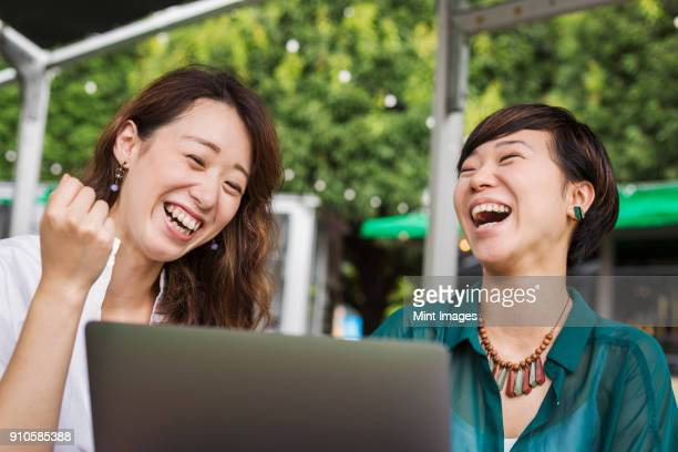 two women with black hair wearing green and white shirt sitting in front of laptop at table in a street cafe, laughing. - 白いシャツ 女性 ストックフォトと画像
