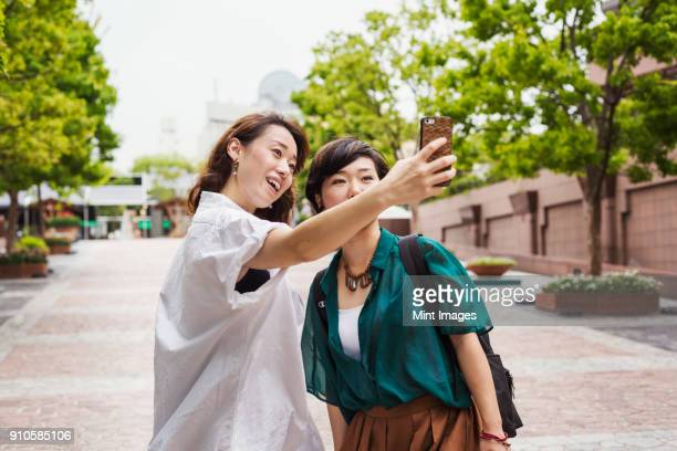 Two women with black hair wearing white and green shirt standing outdoors, taking selfie with mobile phone, smiling.