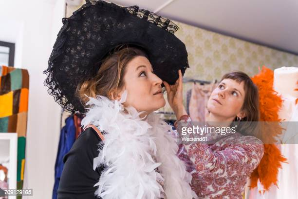 Two women with black hat in a second hand shop
