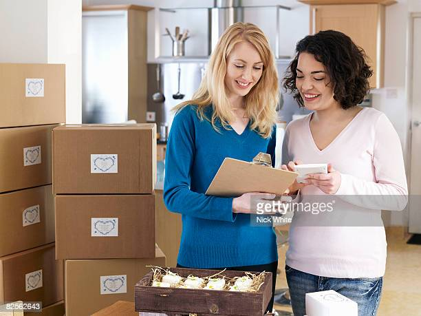 Two women with boxes in kitchen