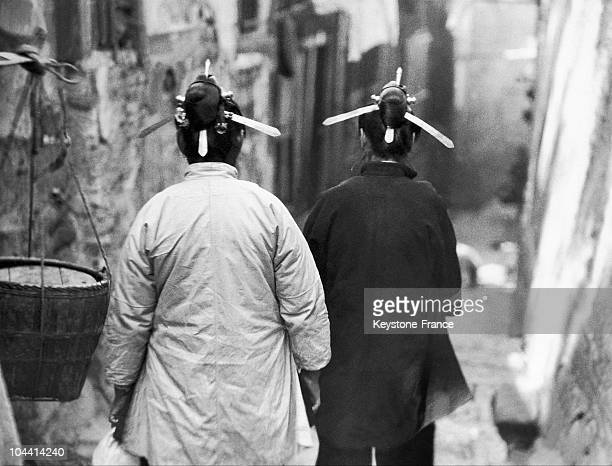 Two women with buns crossed with sticks in the Foochow district in Southern China around 19301939This traditional hairstyle aimed to protect women...