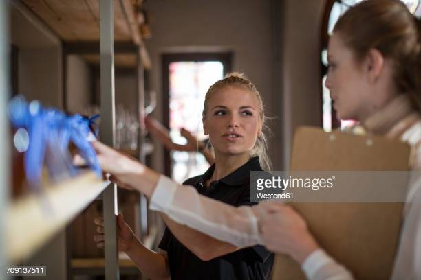 Two women with clipboard talking at shelf