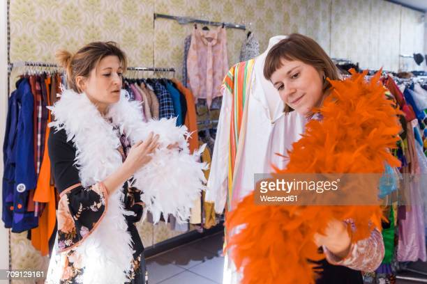 Two women with feather boas in a second hand shop