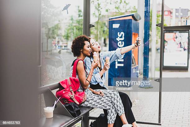 Two women with icecream cones sitting at bus stop taking selfie with smartphone