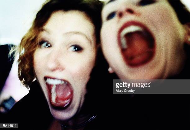 two women with mouths wide open - 頭をそらす ストックフォトと画像