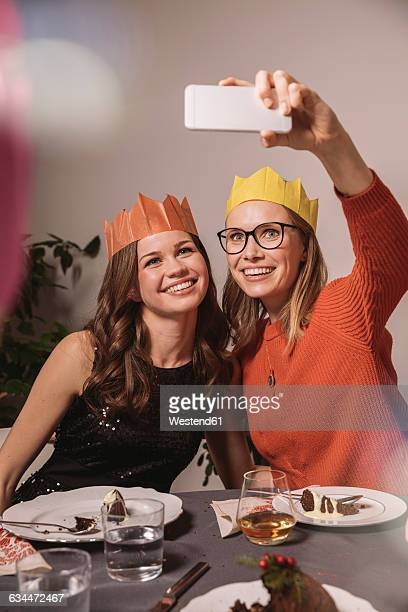 Two women with paper crowns taking a selfie while having Christmas pudding