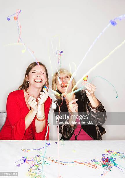 Two women with party poppers