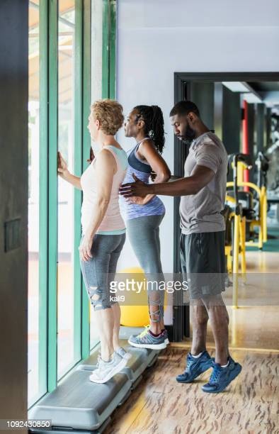 Two women with personal trainer at gym, calf raises