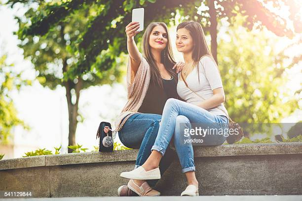 two women with phone in the park