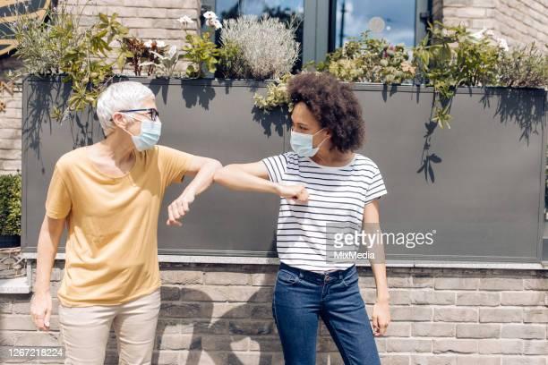due donne con maschere protettive per il viso che salutano con i gomiti - bella ciao foto e immagini stock