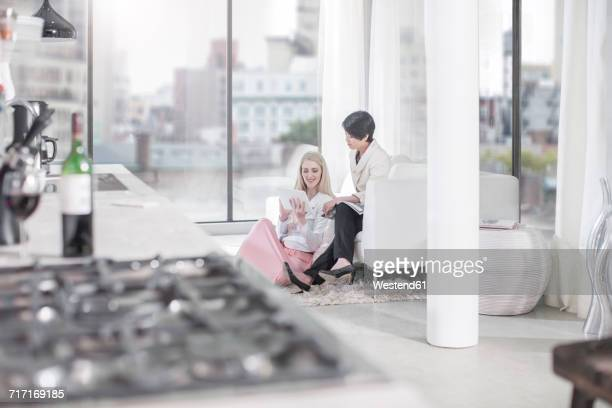 Two women with tablet and magazine in living room