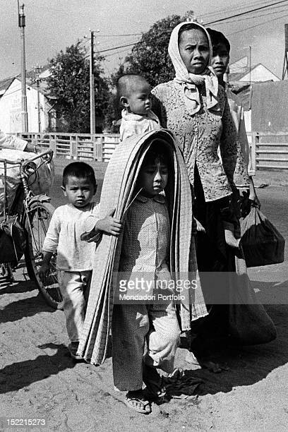 Two women with their children leaving a city torn apart by the conflict Saigon 1968
