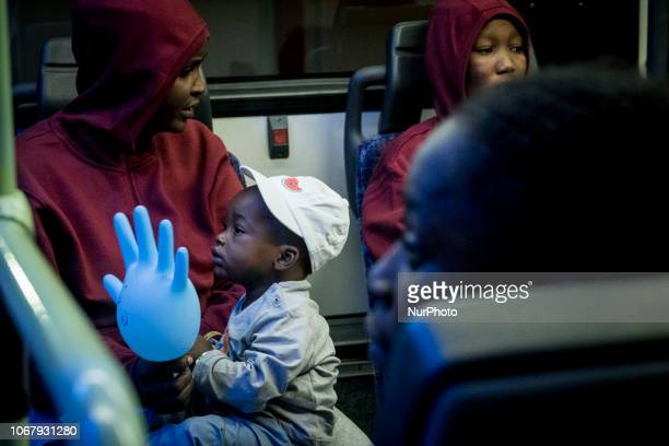 Two women with their young children inside of the bus to be transferred to a center on November 28 Malaga