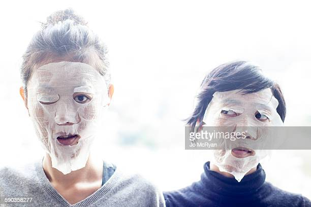 Two Women with Tissue covering face