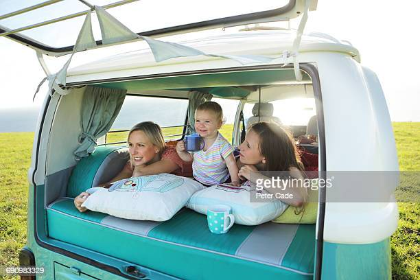 two women with toddler in back of camper van - camper van stock pictures, royalty-free photos & images
