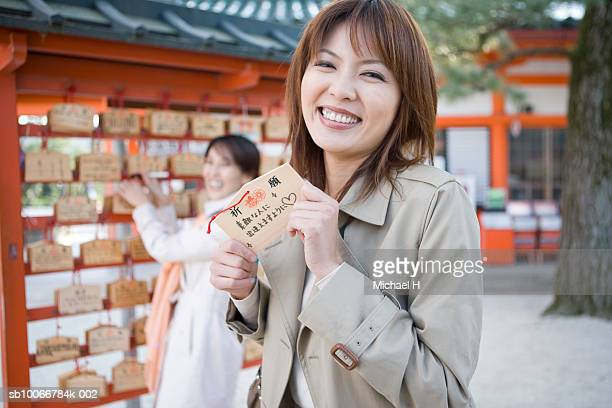 Two women with traditional Japanese New Year's praying blocks