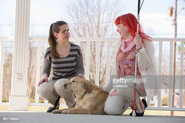 Two women with visual impairments, one with a service dog and one with a cane