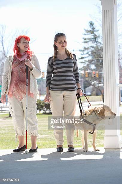two women with visual impairments, one with a service dog and one with a cane - 盲目 ストックフォトと画像