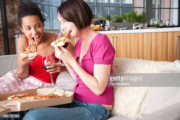 Two women with wine and pizza in a living room