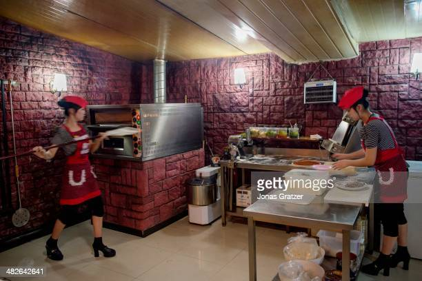Two women work in the back of a pizza parlour in Pyongyang 60 years after the Korean War it is clear that not much has changed in North Korea The...