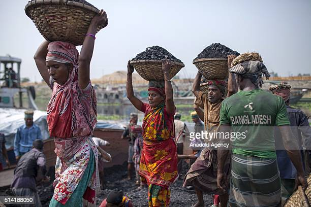 Two women workers carry baskets filled with coal on their heads in the Gabtoli region of Dhaka Bangladesh on March 7 2016 Bangladeshi women work at...