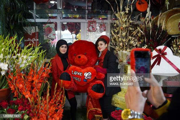 Two women working for Afghan Mitra TV pose wiht a doll on Valentine's Day in Kabul on February 14 2020