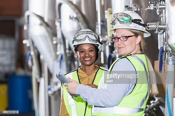 Duas mulheres a trabalhar em Uma fábrica com hardhats