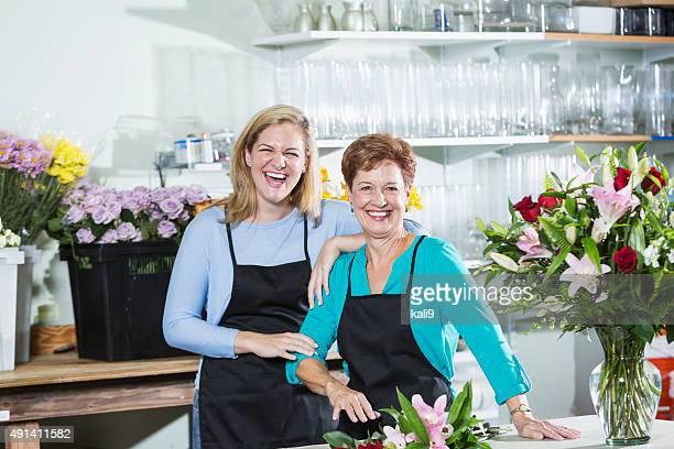 Two women working in a flower shop wearing aprons