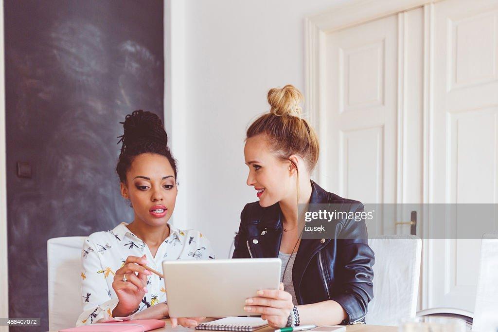 Duas mulheres trabalhando em tablet digital no escritório : Foto de stock