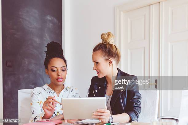 duas mulheres trabalhando em tablet digital no escritório - persuasão - fotografias e filmes do acervo
