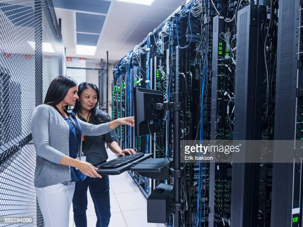 two women working with computer in server room - data center stock pictures, royalty-free photos & images