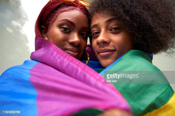 two women wrapped in pride flag - orgoglio foto e immagini stock