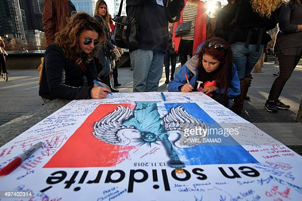 Two women write their condolences on a sign during a vigil at the 9/11 memorial in New York on November 16 for the victims of the Paris terrorist...