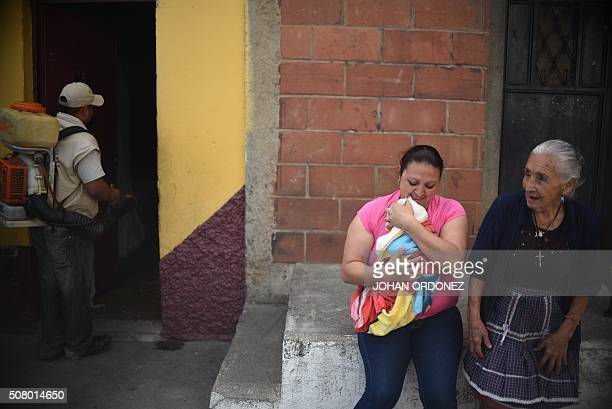 Two womenn leave their home while a Health ministry worker fumigates her home against the Aedes aegypti mosquito vector of the dengue Zika and...