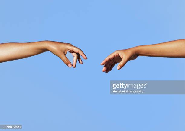 two women's arms outstretched reaching toward each other - reaching stock pictures, royalty-free photos & images