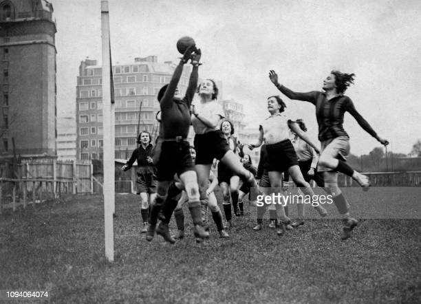 Two women's football team fight for the ball during a match between Fémina Sport and Hirondelles on December 25, 1934. - Fémina Sport is a women's...