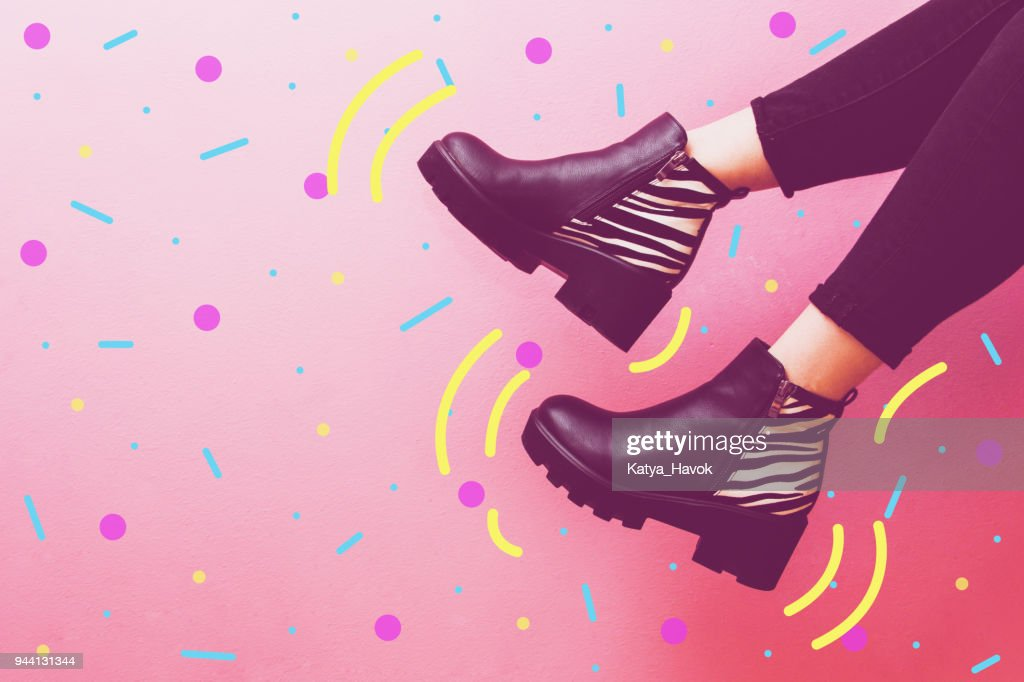 two women's legs dangle in fashionable boots. : Stock Photo