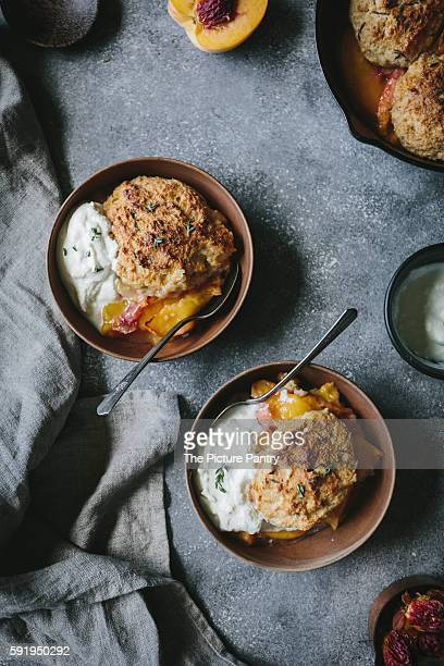 Two wood bowls filled with peach cobbler and honey swirled ricotta and thyme are photographed from the top view.