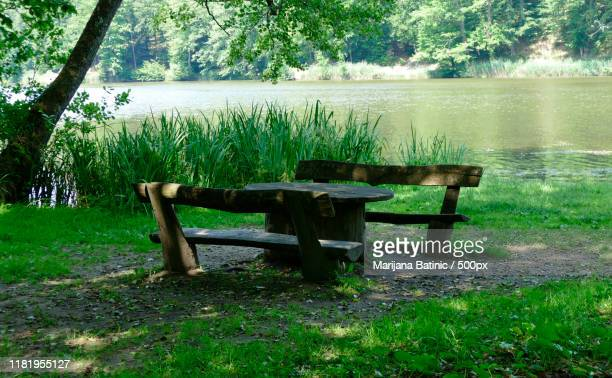 two wooden benches and wooden table by lake shore - marijana stock pictures, royalty-free photos & images