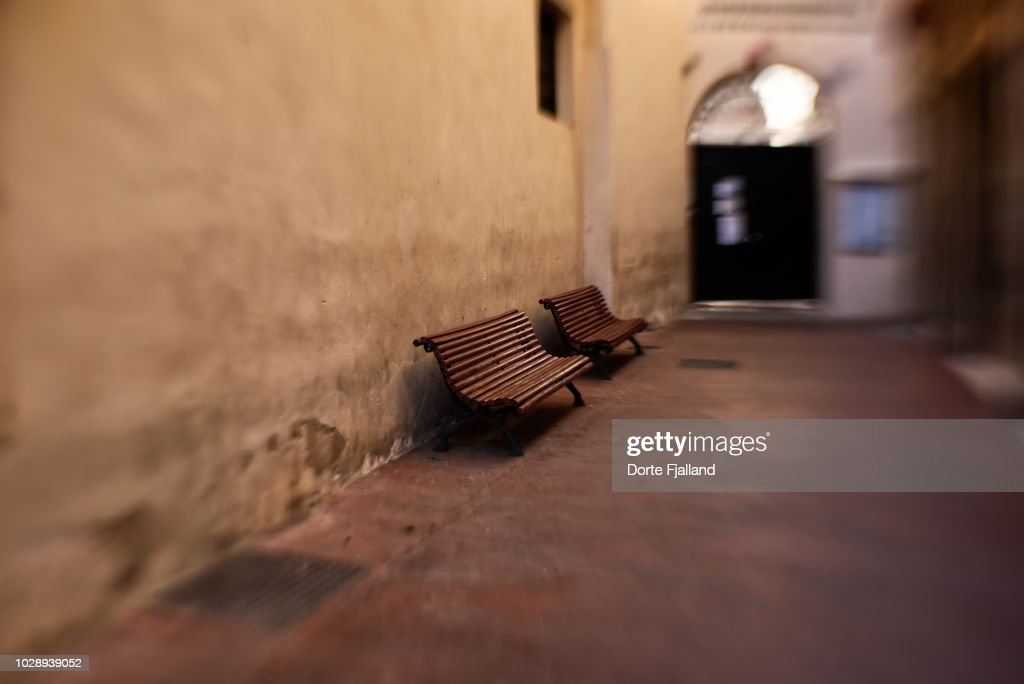 Two wooden benches in a dark corridor with a closed door at the end : Foto de stock