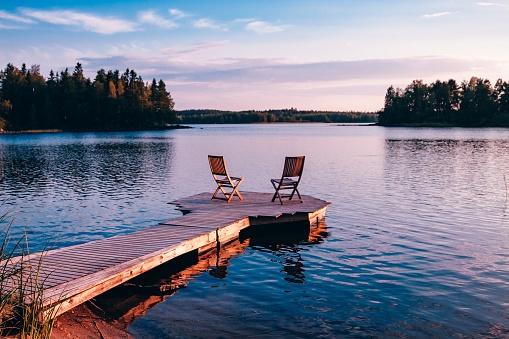 Two wooden chairs on a wood pier overlooking a lake at sunset 955099970