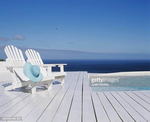 two wooden chairs on decking by outdoor pool - ウッドデッキ ストックフォトと画像