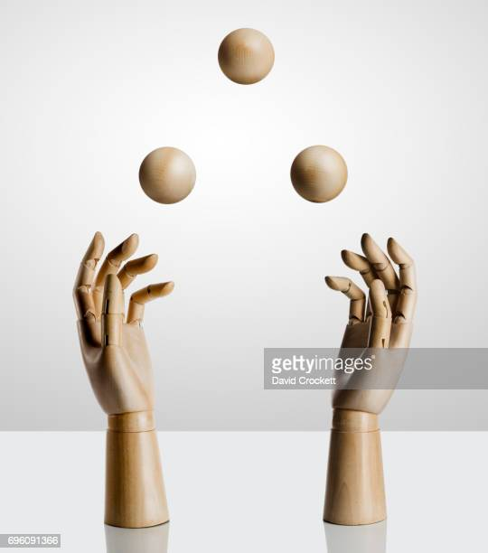 Two wooden hands juggling wood shapes