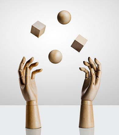 Two wooden hands juggling wood shapes - gettyimageskorea
