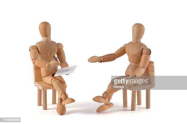 Two wooden mannequin placed as if having a conversation