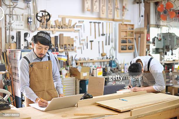 Two woodworkers making furniture in workshop
