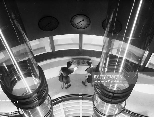 Two workers adjust a dial in a futuristic control room in the film 'Things to Come' directed by William Cameron Menzies for London Films