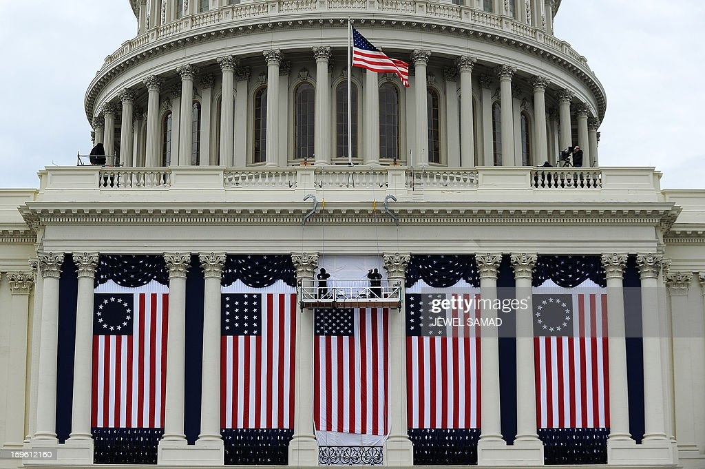 Two workers adjust US flags on the US Capitol as preparations continue for the second inauguration of US President Barack Obama in Washington, DC, on January 17, 2013. Obama faces a near impossible task in his second inaugural address on January 21: uniting a nation in which the compromise that oils governing is crushed by deep political divides. Before a crowd of thousands and the eyes of the world on television and online, Obama will stand on the West Front of the US Capitol and swear to faithfully execute the office of president and defend the Constitution. AFP PHOTO/Jewel Samad