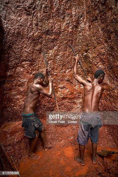 Two workers are chipping the earth from the side of their concession plot using heavy iron bars 28 March 2013 near an Angolan village not far from...