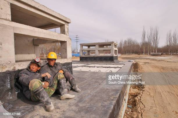 Two workers are pictured near the suspended construction site of Shiji Luyuan Metro Station, the start of the city's subway system, in Baotou city,...